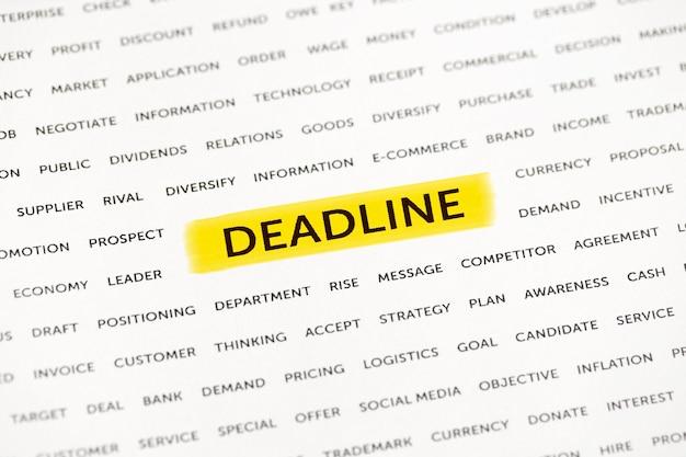Le mot «date limite» est mis en évidence avec un marqueur sur papier. concept d'entreprise, stratégie, planification, succès