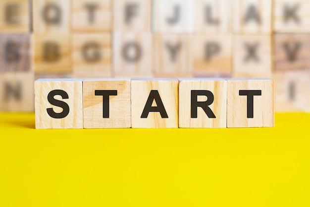 Le mot début est écrit sur des cubes en bois sur une surface jaune vif. en arrière-plan, des rangées de cubes avec des lettres différentes. concept commercial et financier