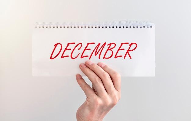 Mot de décembre sur le planificateur en main masculine sur fond blanc.