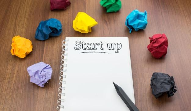 Mot de démarrage sur le cahier avec du papier coloré froissé et un stylo sur la table en bois