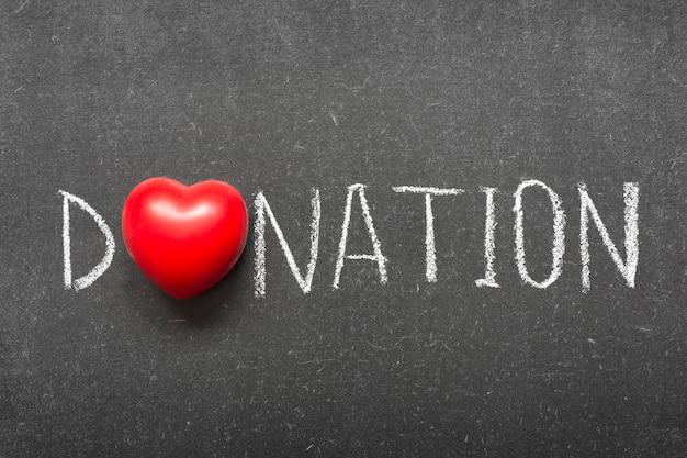 Mot de don écrit à la main sur le tableau noir de l'école avec le symbole du coeur au lieu d'o
