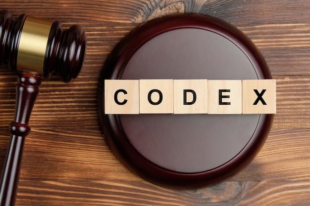 Mot du codex sur des blocs de bois à côté de juge marteau