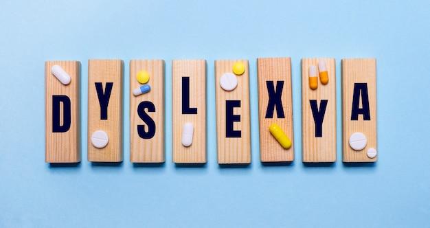 Le mot dyslexia est écrit sur des blocs de bois sur une table bleu clair près des pilules