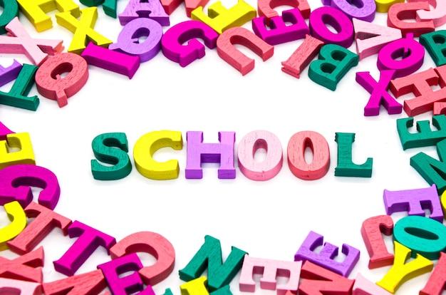 Le mot «école» est composé de lettres multicolores en bois entourées de lettres colorées dispersées sur fond blanc.