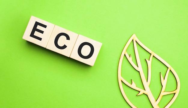Mot écologique sur des blocs de bois avec feuille de bois sur fond vert