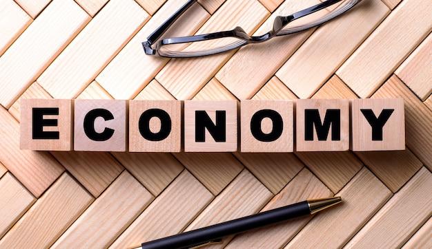 Le mot économie est écrit sur des cubes en bois sur un fond en bois à côté d'un stylo et des lunettes.