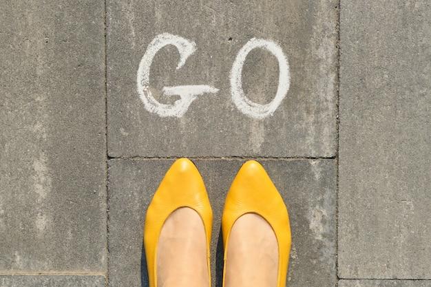 Mot écrit sur un trottoir gris avec des jambes de femmes, vue de dessus