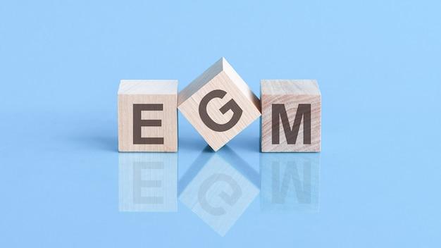 Le mot egm est composé de blocs de construction en bois posés sur la table bleue, concept