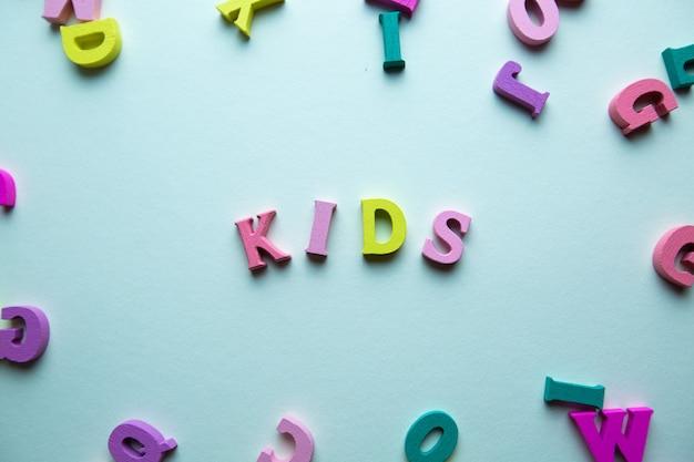 Le mot enfants est composé de lettres multicolores en bois sur fond bleu pour enfants