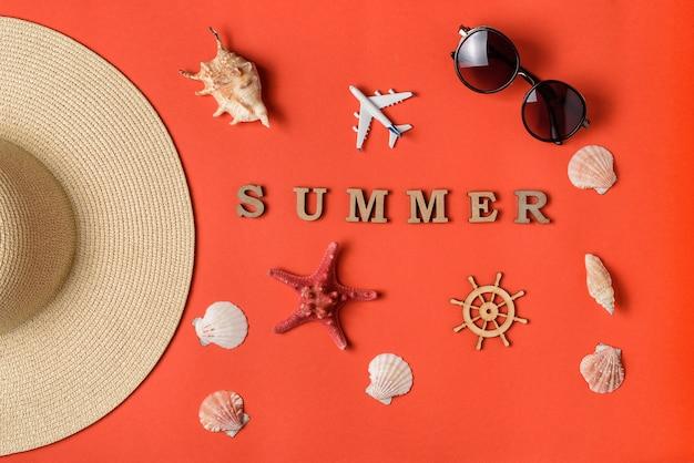 Mot d'été de lettres en bois. coquillages, avion, partie de chapeau, lunettes de soleil et volant. fond de corail vivant. mise à plat. concept de voyage