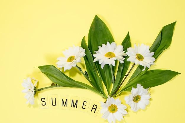 Le mot été et marguerites sur fond jaune