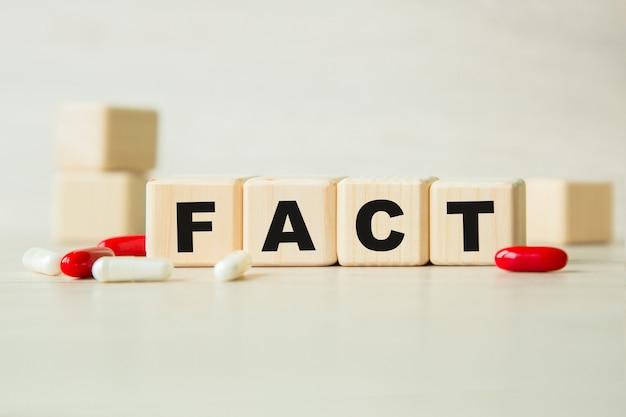 Le mot fact est écrit sur une structure de cubes en bois avec des tablettes.
