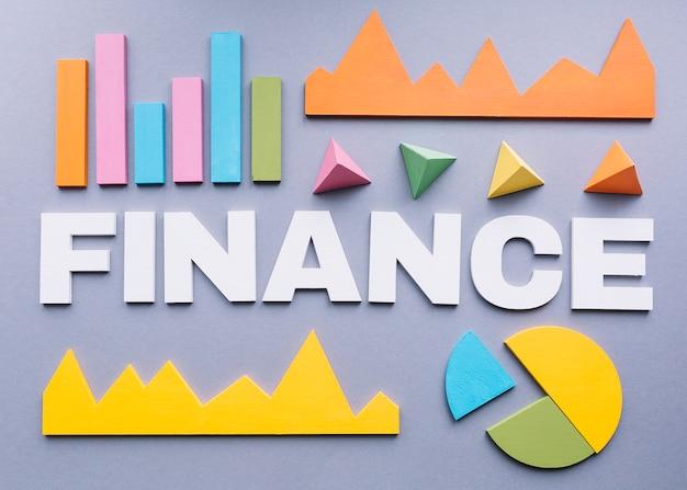 Mot finance entouré de nombreux graphiques sur fond gris