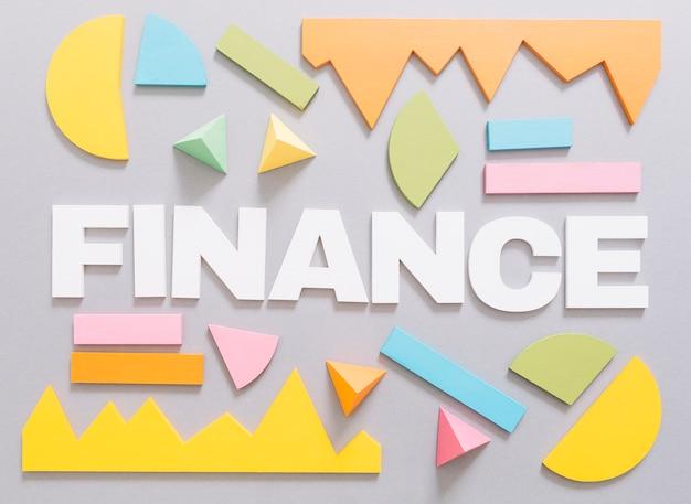 Mot de la finance avec graphique coloré et formes géométriques sur fond gris