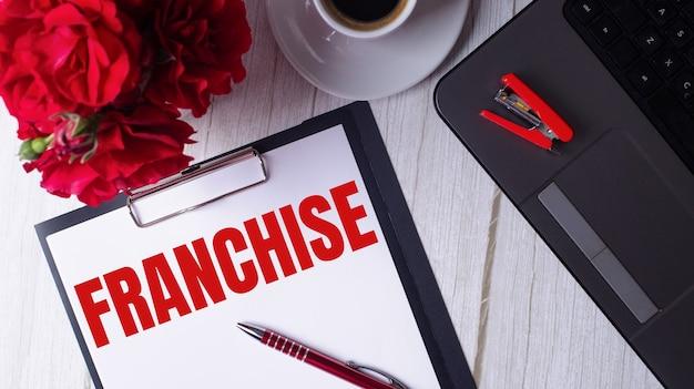 Le mot franchise est écrit en rouge sur un bloc-notes blanc près d'un ordinateur portable, d'un café, de roses rouges et d'un stylo.