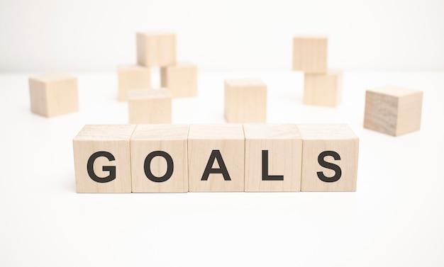 Le mot goals est écrit sur une structure de cubes en bois. blocs sur un fond blanc clair.