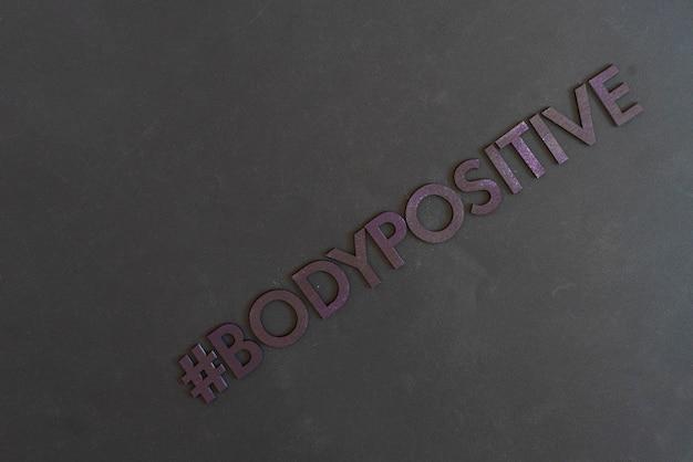 Un mot hashtag positif pour le corps, des lettres découpées, un concept à la mode d'icône abstraite
