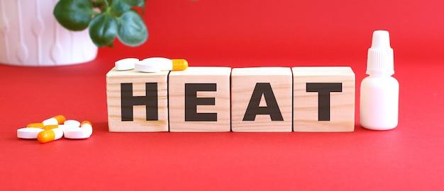 Le mot heat est composé de cubes en bois sur fond rouge avec des médicaments.