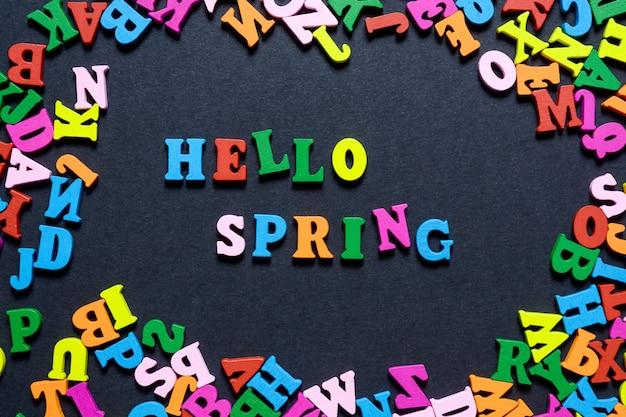 Le mot hello on spring issu de lettres en bois multicolores sur fond noir, idée créative