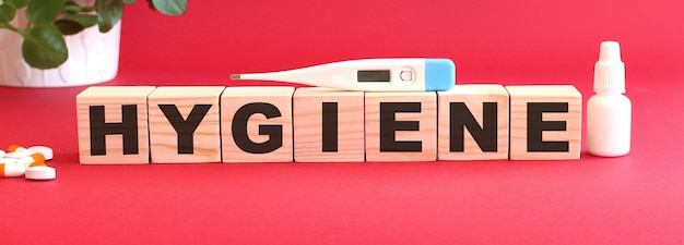 Mot hygiène fait de cubes en bois sur fond rouge