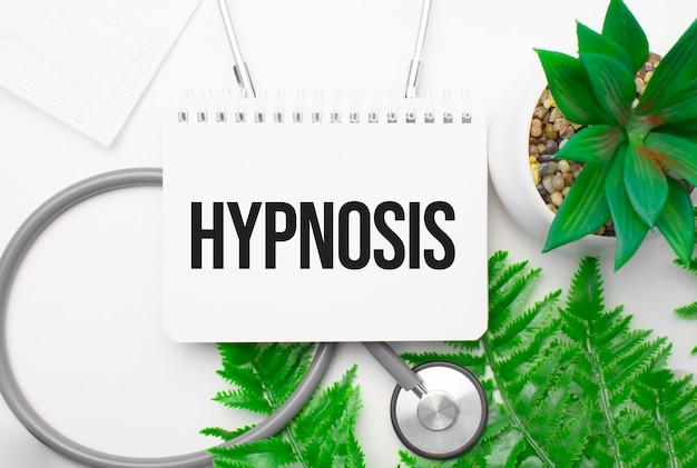 Mot d'hypnose sur ordinateur portable, stéthoscope et plante verte