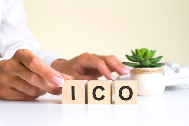 Le mot ico, orthographié sur des cubes en bois avec des lettres sur un fond blanc ico - abréviation de initial coin offering