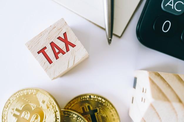 Mot de l'impôt sur le cube en bois avec des objets comme pièce d'or, une calculatrice et un mini modèle de maison derrière un fond propre blanc. concept de propriété de prêt financier commercial.mot fiscal sur le cube en bois.