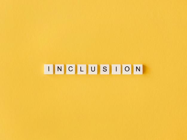 Mot d'inclusion écrit en lettres de scrabble sur fond jaune