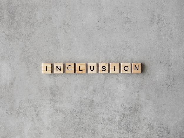 Mot d'inclusion écrit en lettres de scrabble sur fond de marbre