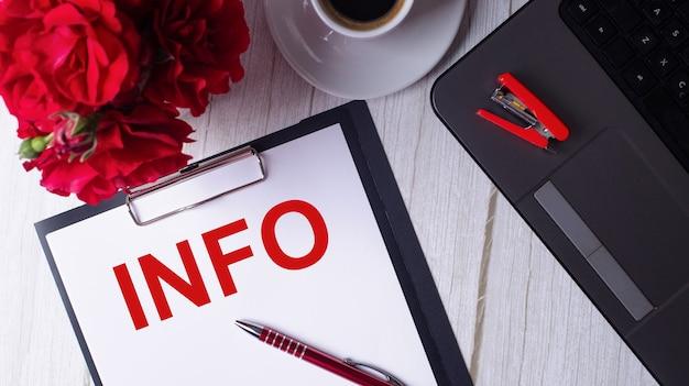 Le mot info est écrit en rouge sur un bloc-notes blanc près d'un ordinateur portable, d'un café, de roses rouges et d'un stylo.