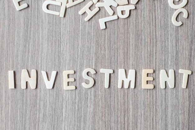 Mot d'investissement de lettres de l'alphabet en bois. concept d'affaires et d'idée