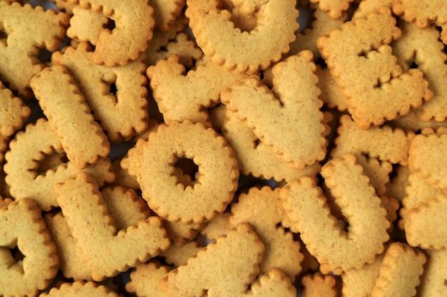 Le mot je t'aime orthographié avec des biscuits en forme d'alphabet sur le tas de ces mêmes biscuits