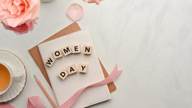 Dés avec le mot «journée de la femme» sur des cahiers décorés de fleurs roses, ruban et espace copie sur table en marbre