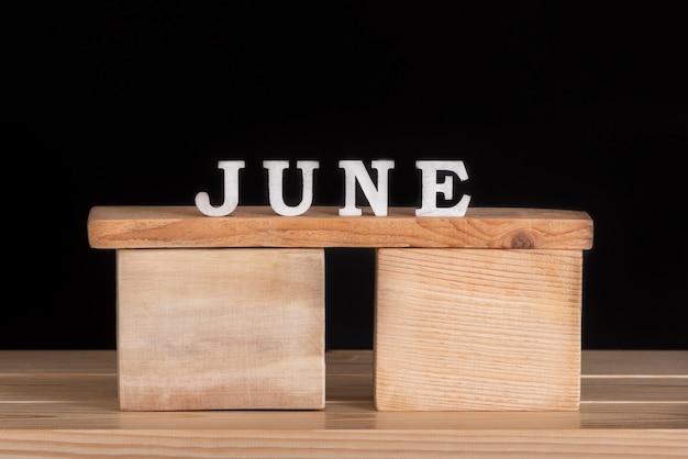 Mot juin par composition de lettres en bois