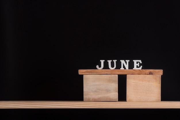 Mot juin par lettres en bois