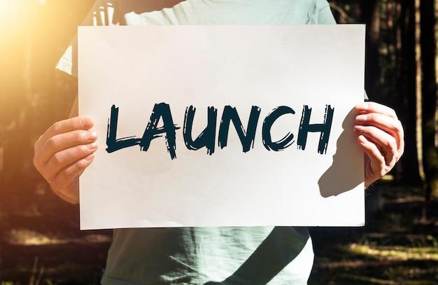 Mot de lancement sur une pancarte en papier dans les mains des hommes dans le concept de forêt de démarrage de la vie écologique verte