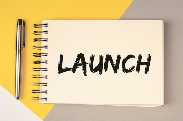 Mot de lancement sur papier bloc-notes sur fond jaune et gris