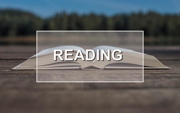 Mot de lecture sur un livre de papier ouvert sur bois dans la nature estivale