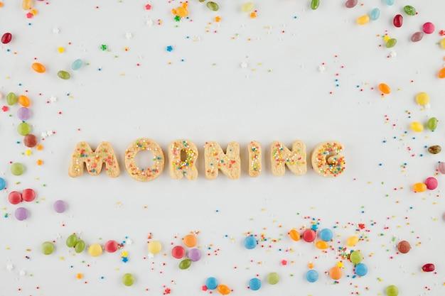 Mot matin fait de biscuits au sucre maison décorés sur une surface blanche avec des bonbons sucrés et des paillettes