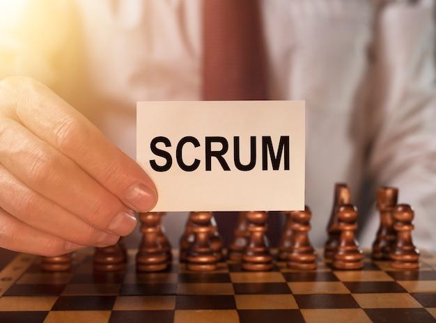 Mot de mêlée sur papier dans la main de l'homme d'affaires se bouchent sur le concept d'échiquier des méthodes de gestion