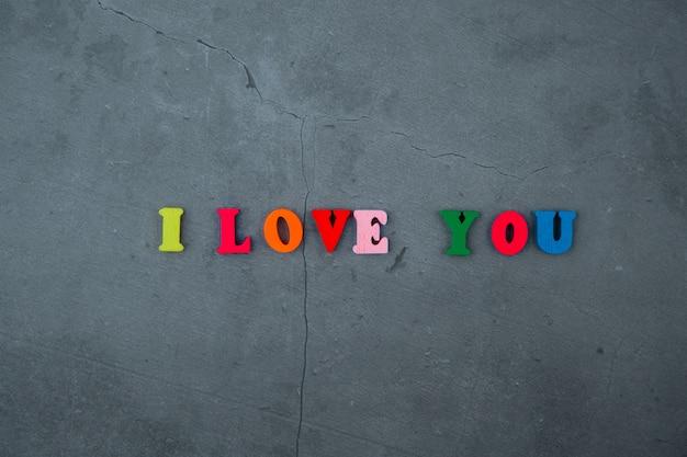 Le mot multicolore je t'aime est fait de lettres en bois sur un mur de plâtre gris.