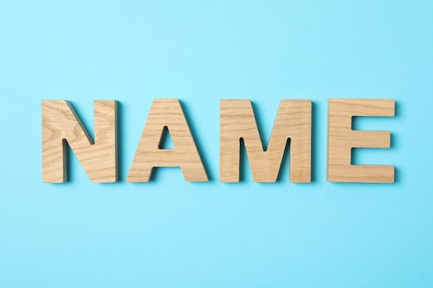 Mot de nom fabriqué à partir de lettres en bois sur fond bleu