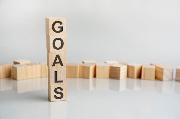Le mot objectifs, sur des cubes en bois sur fond gris. croissance des investissements financiers ou décision d'investissement dans le concept d'entreprise