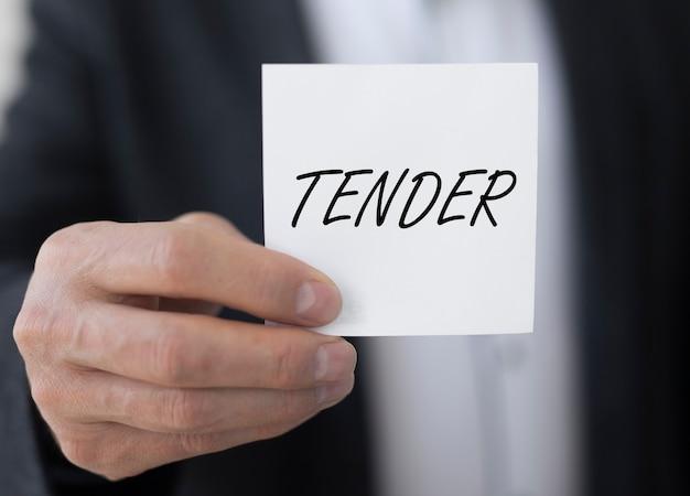 Mot d'offre sur une note papier dans la main d'un homme d'affaires offrant des marchés publics