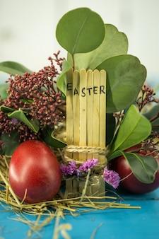 Le mot pâques dans le bloc de texte conceptuel sur des bâtons en bois, de beaux œufs de fête avec des verts