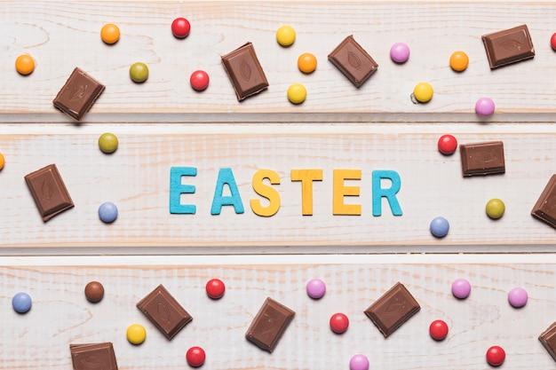 Mot de pâques entouré de pierres précieuses multicolores et de morceaux de chocolat sur une table en bois