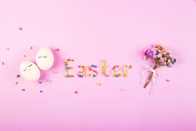 Le mot pâques est écrit en petites fleurs colorées sur fond violet.