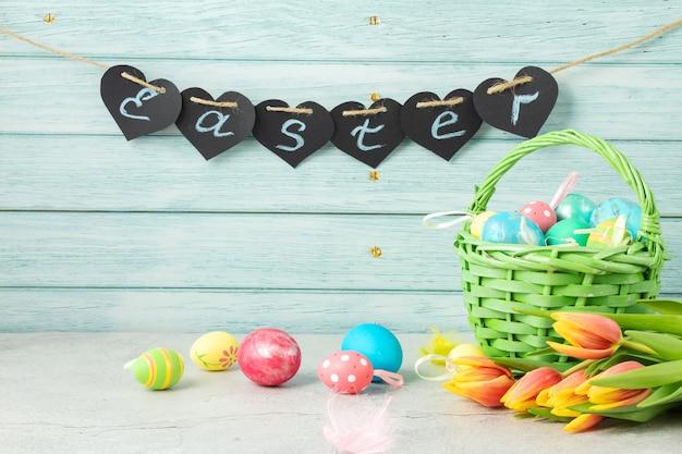 Le mot pâques sur un mur en bois, oeufs de pâques dans un panier et fleurs tulipes