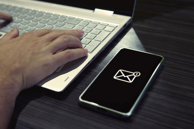 Mot de passe sms pour l'accès au réseau sur le téléphone lors de la saisie sur un ordinateur portable. icône générique de courrier sur smartphone à écran noir allongé sur la table de bureau à proximité d'un homme qui travaille. recevoir des messages tout en étant en ligne