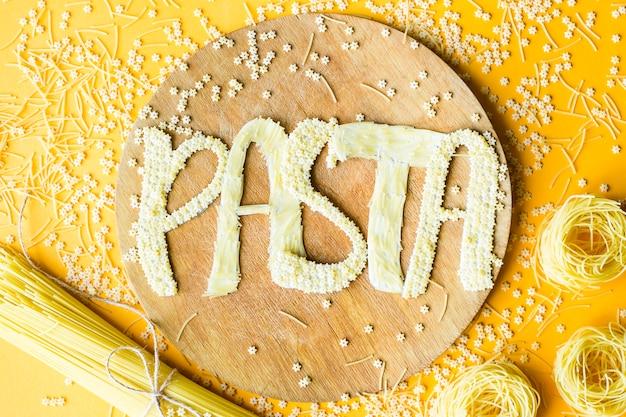 Le mot pâtes est écrit en lettres volumineuses à partir de petits macaronis crus